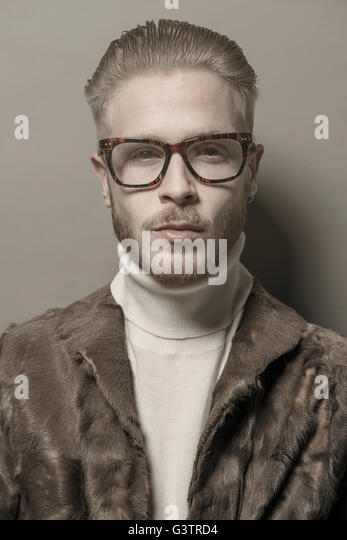 Studio portrait of a cool young man with glasses wearing a fur jacket. - Stock Image