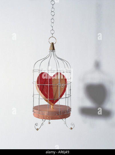 Wooden love heart hanging trapped in a metal birdcage, heart painted half red, solid wooden base - Stock-Bilder