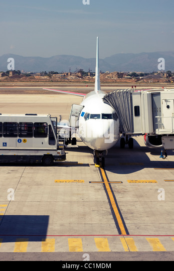 Passenger airplane being serviced at the gate - Stock Image