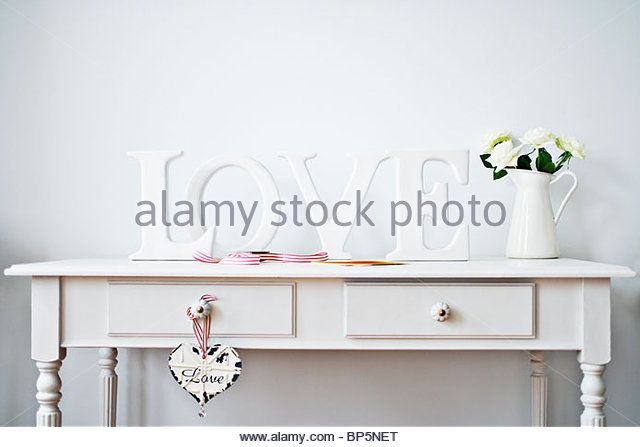 'Love' decorations, ribbon, roses and card on desk - Stock-Bilder