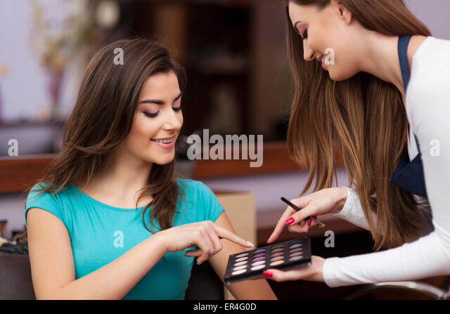 Woman with makeup artist choosing color of eyeshadow. Debica, Poland - Stock Image