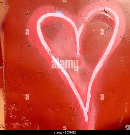 Heart graffiti on a red wooden background in Burlington, Vermont. - Stock Image
