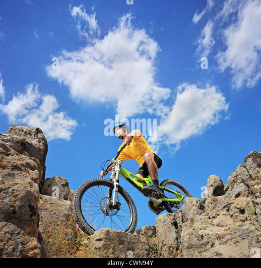 A person riding a mountain bike on a sunny day, low angle view - Stock Image