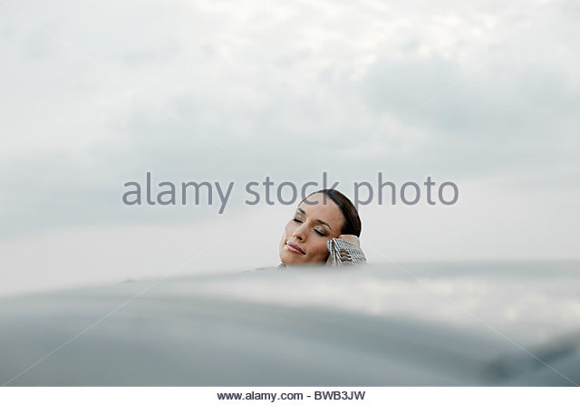 Businesswoman leaning on car roof with eyes closed - Stock Image