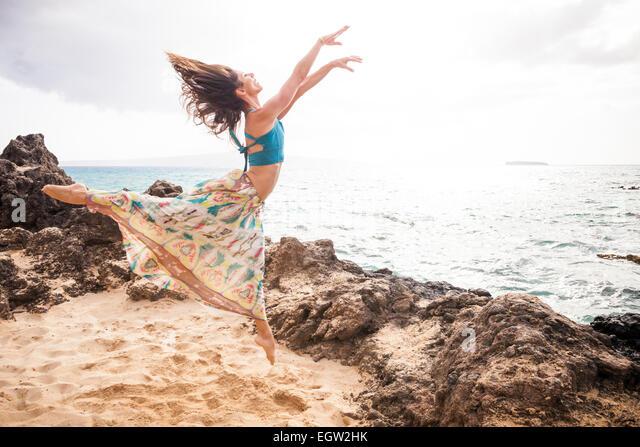 Woman dancing and jumping on beach. - Stock-Bilder