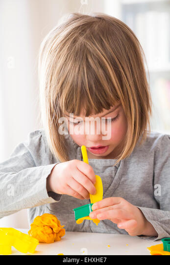 Little girl cutting out modeling clay - Stock Image