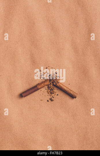 Quit smoking concept, broken cigarette top view over brown paper, warm retro image tone. - Stock Image