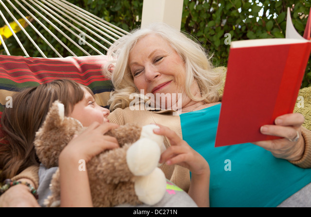 Grandmother and granddaughter reading book in hammock - Stock-Bilder