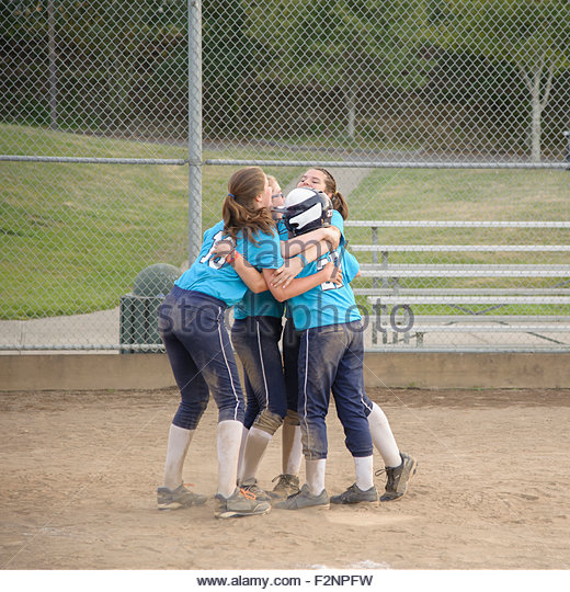Softball team hugging on field - Stock-Bilder