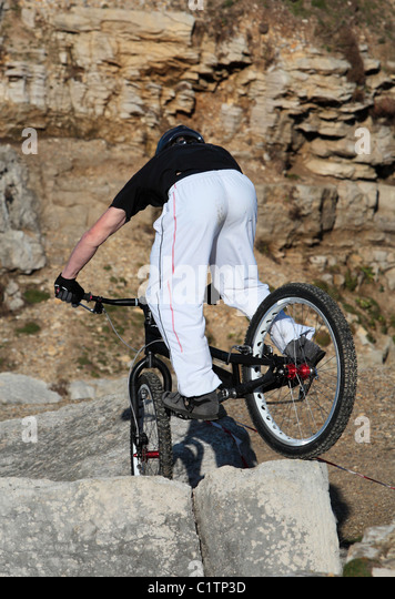 A young man on a mountain bike enjoys riding over some tough rocks - Stock Image