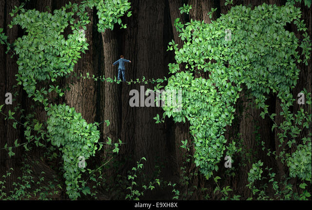 Global growth risk business concept as a businessman walking on a tightrope made from plant vines in a background - Stock-Bilder