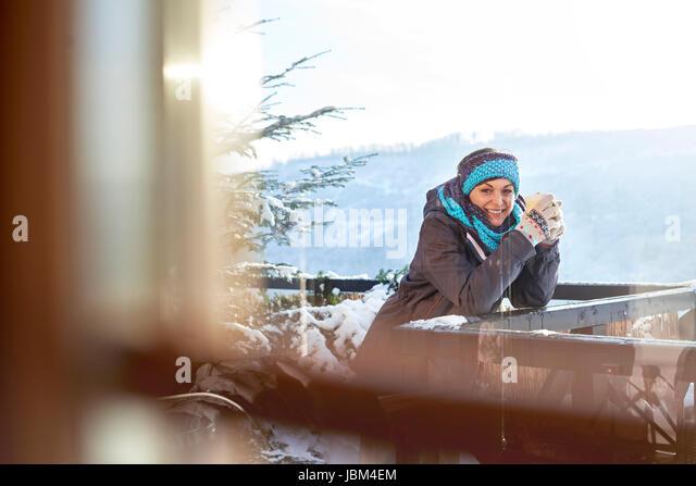Portrait smiling female skier drinking hot cocoa on sunny cabin balcony - Stock-Bilder
