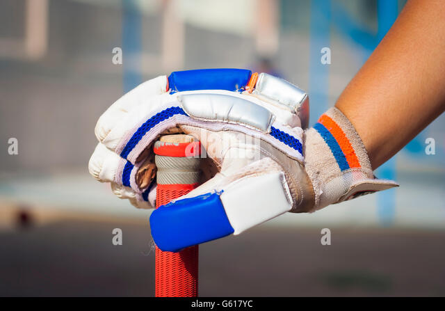 Caucasian boy holding cricket bat & glove.isolated, selective focus, shallow depth of field, concept of sports - Stock-Bilder