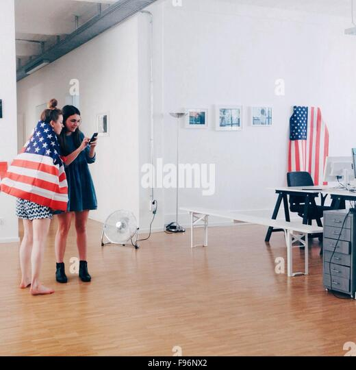 Full Length Of Young Women With American Flag Using Mobile Phone In Office - Stock Image