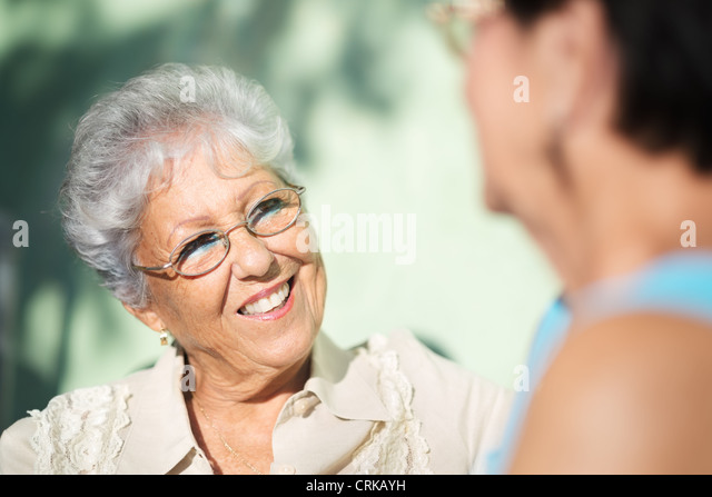 Active retirement, two elderly female friends talking on bench in public park - Stock Image