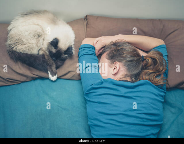 A young woman is sleeping in a bed with a cat next to her - Stock Image