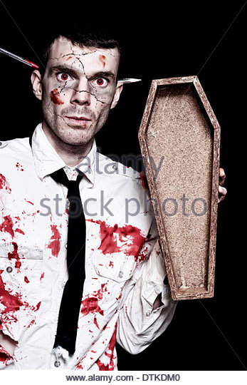 Halloween Businessman Covered In Blood Holding Open Funeral Casket On Black Background - Stock Image