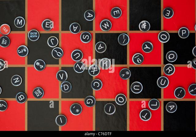 random assortment of typewriter keys on checker board - Stock Image