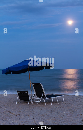 Full Moon Rising over as set of beach chairs and umbrella on the Beach on Amelia Island in Florida. - Stock Image