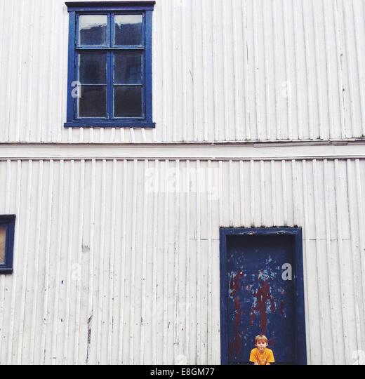 Norway, Fredrikstad, Boy (10-11) sitting against house - Stock Image