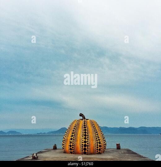 Famous yellow pumpkin with black dots by Japanese artist Yayoi Kusama installed on the pier on Naoshima Island - Stock Image