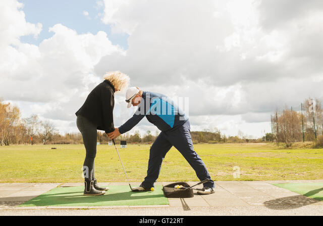 Man teaching friend to play golf at driving range - Stock-Bilder