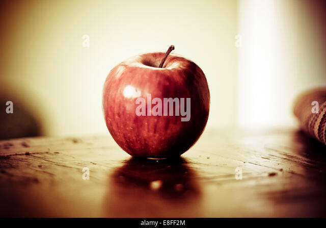 Close-up of red apple on wooden table - Stock Image