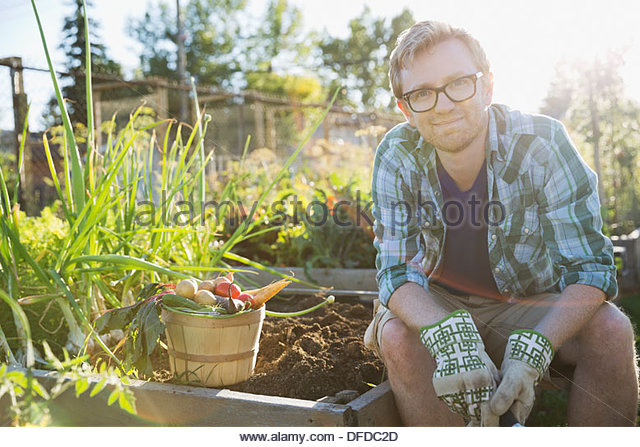 Portrait of confident man sitting in community garden - Stock Image