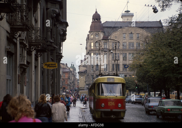 Ukraine L'vov L'viv streetcar trolley pedestrians residents buildings - Stock Image