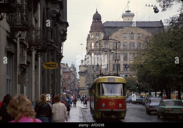 Ukraine L'vov L'viv streetcar trolley pedestrians residents buildings - Stock Image