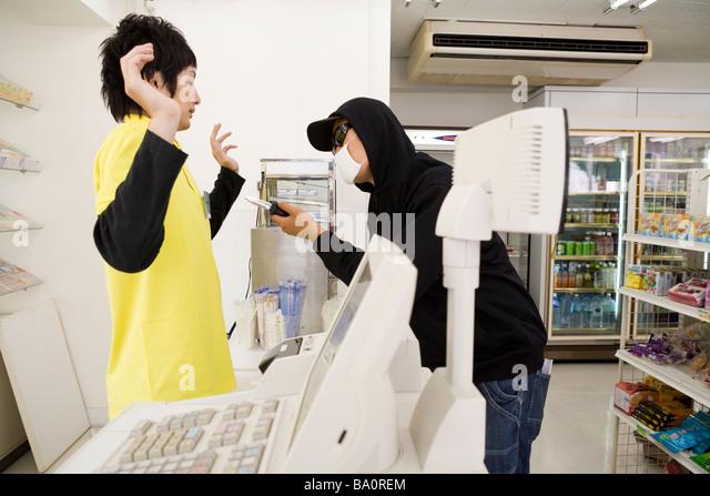 Robber threatening convenience store clerk - Stock-Bilder