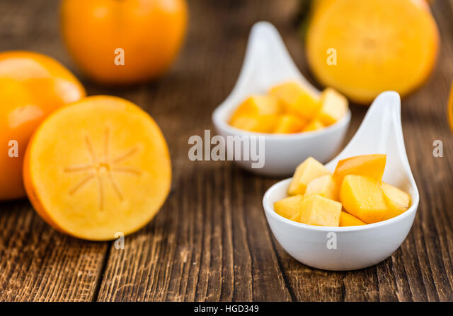 Portion of fresh made Kaki fruits (close-up shot; selective focus) - Stock Image