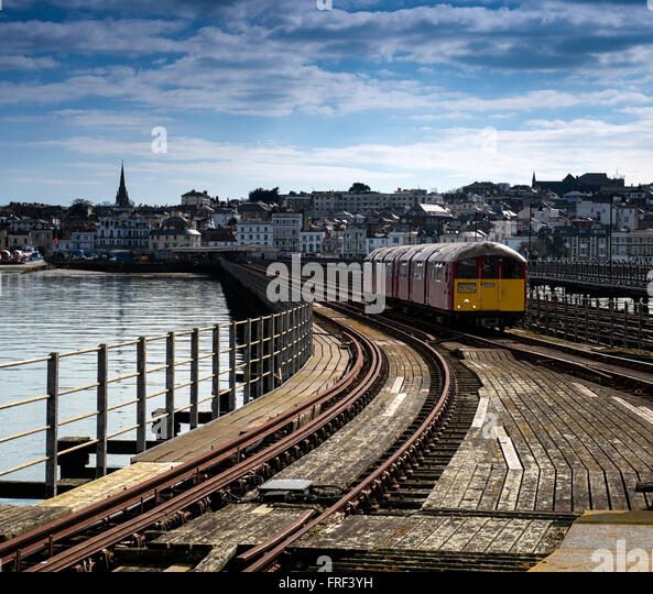 An old London Underground Tube train approaches Ryde Pier Head on the Island Line, Isle of Wight - Stock Image