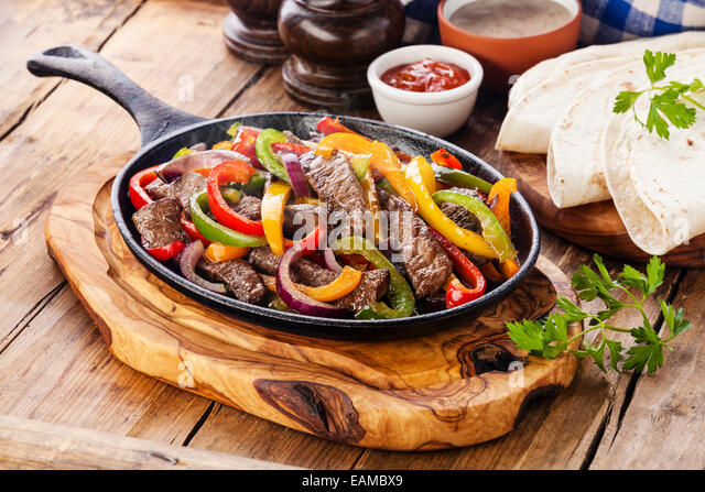 Beef Fajitas with colorful bell peppers in pan and tortilla bread and sauces - Stock Image