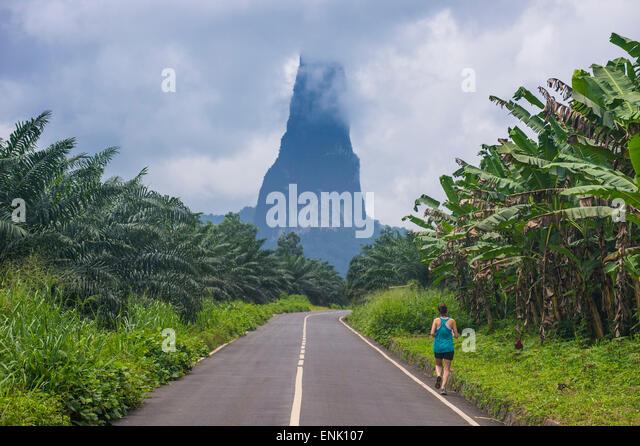 Runner on a road leading to the unusal monolith, Pico Cao Grande, east coast of Sao Tome, Sao Tome and Principe, - Stock Image