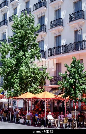 Madrid Spain Europe Spanish Atocha El Brillante restaurant alfresco dining tables umbrellas building Mediodia hotel - Stock Image