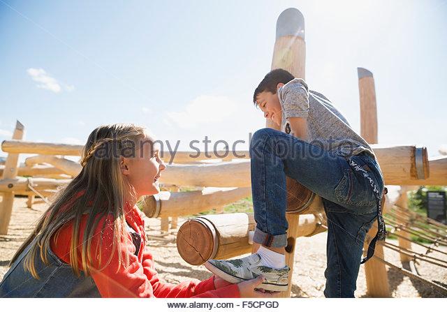 Girl helping boy climb logs at sunny playground - Stock Image