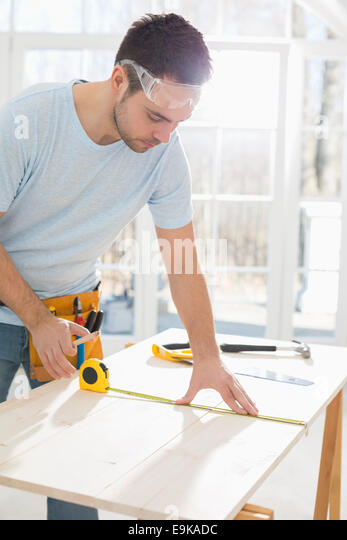 Mid-adult man marking table with measure tape - Stock Image