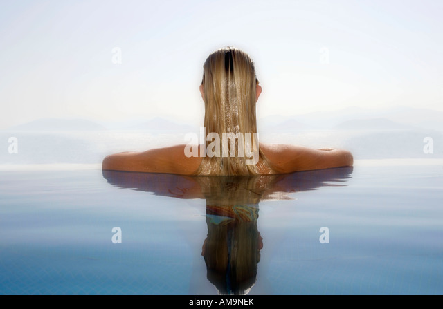 Woman leaning at the ledge of an infinity pool. - Stock Image