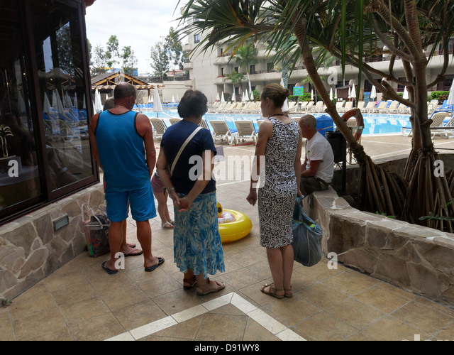 Tourists patiently waiting for a swimming pool to open at 10am in Adeje Tenerife Canary Islands Spain, a British - Stock Image