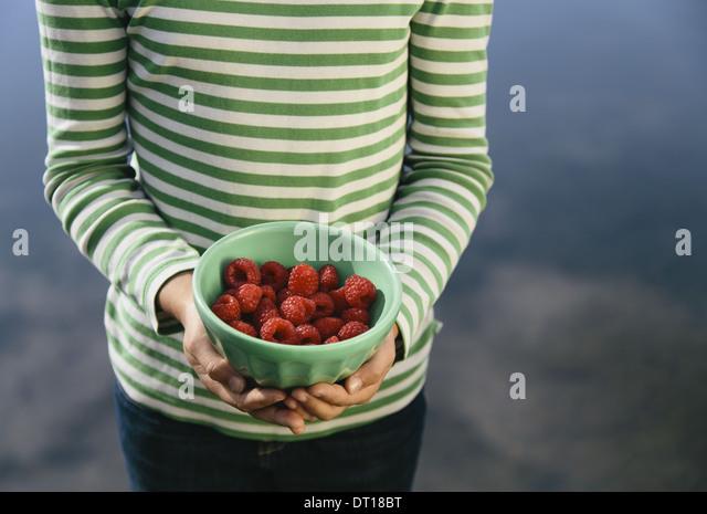 Seattle Washington USA Nine year old girl bowl of organic raspberries - Stock Image