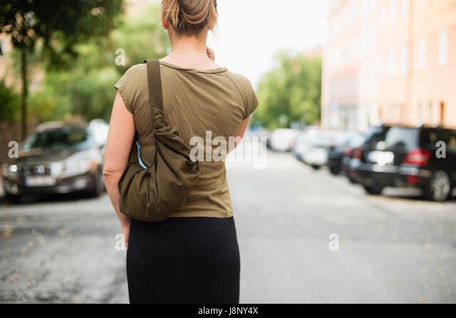 Woman walking in street - Stock-Bilder