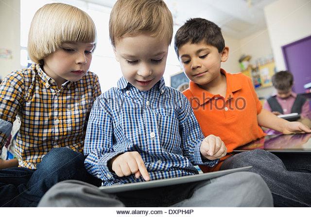 Schoolboy using digital tablet in elementary classroom - Stock Image