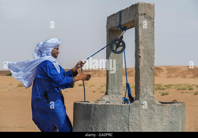 Moroccan man dressed in a traditional gandora at a well in the Sahara desert. - Stock Image