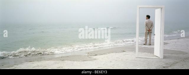 Man on beach admiring view, seen through open door - Stock Image