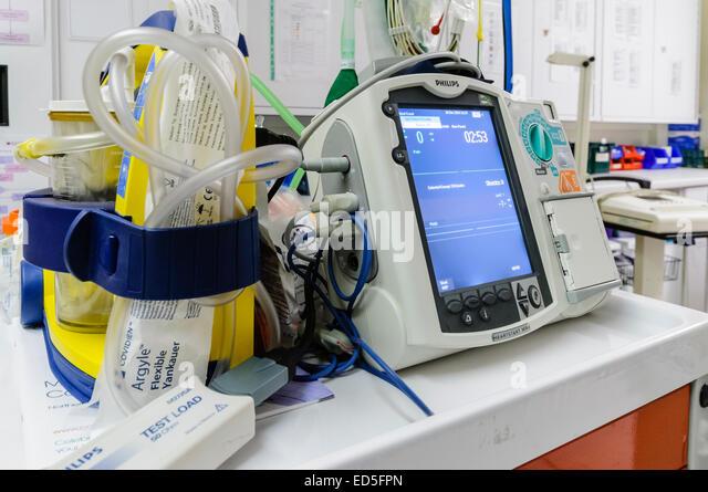 Defibrillator sitting ready for use on a hospital Crash Trolley. - Stock Image