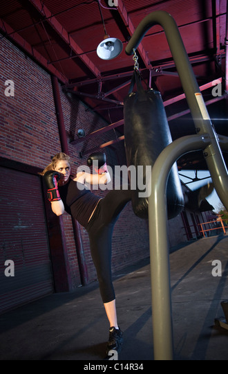 A teenage girl trains for mixed martial arts outside a warehouse in Birmingham, Alabama. - Stock Image