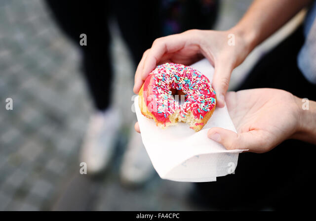 Cropped image of woman holding donut during festival - Stock-Bilder