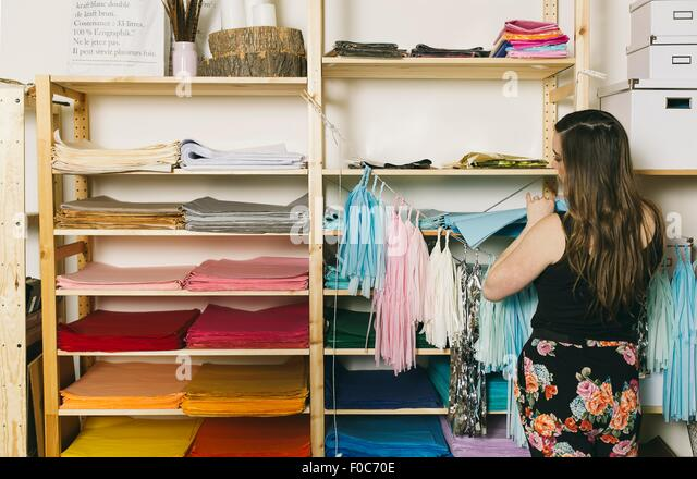 Female textile designer selecting textiles in design studio - Stock Image