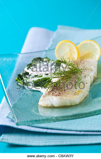 Steam-cooked fish steak with spinach and cream - Stock Image